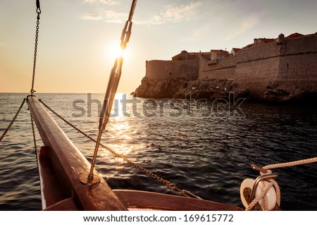 Old sailing ship sails into the sunset next to the city walls of Dubrovnik