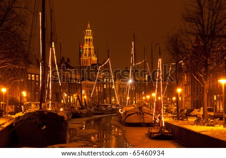 Old sailing ships and A-church with snow at the event 'Winterwelvaart' in Groningen, Holland.