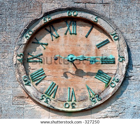 Old sandstone clock face with weathered hands & numbers