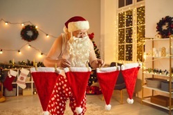 Old Santa Claus hanging his red and white hats to dry on clothesline after doing laundry. Father Christmas at home getting ready for winter holidays and decorating his house