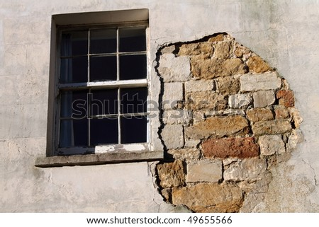 Old sash window and wall with missing render.