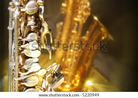 Old saxophone against a bright golden reflective surface with copy space