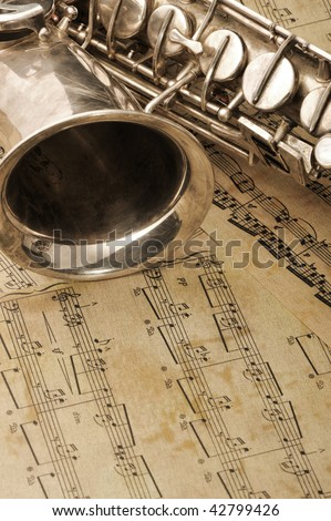 Old saxophone and notes. The Musical instrument laying on notes with classical music of the beginning of 17 centuries