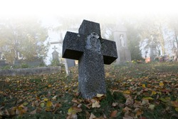 Old scary graves in the cemetery. Spooky tomb stones in a foggy autumn scene in the graveyard. All Saints Day / All Hallows / 1st November. Slovakia