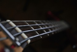 Old school rock bass guitar with cool brown neck at a band's home studio with dark background in a close up photo,