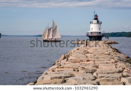 Old Schooner sails past Spring Point lighthouse on a warm summer day in Portland Maine. Windjammers, as they are called, are a favorite tourist attraction in Maine. #1032965290