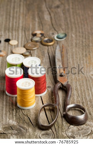Old scissors, colorful cottons and buttons on old wooden table