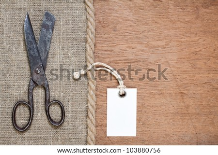 Old scissors on canvas and wood textured background with price tag