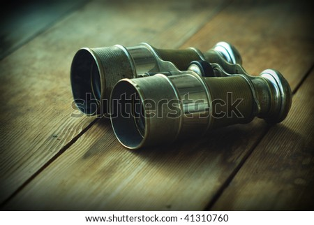 Old sea binoculars isolated on the wooden background