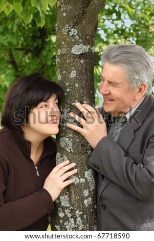 old senior and his adult daughter standing near tree and smiling, hands on trunk, summer