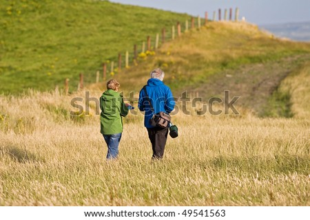 Old senior citizen couple taking a walk in the field in Ireland