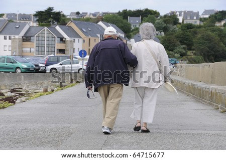 Old senior couple walking together holding their hands