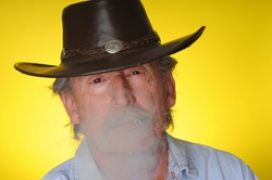 Old senior cowboy smoking a hand rolled cigarette
