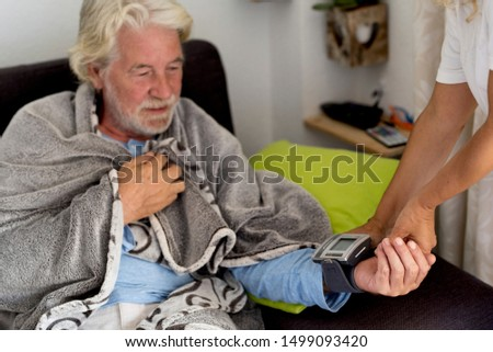 Old senior man at home with bad health issue sitting on the sofa while woman doctor check blood pressure with modern tool - real scene with people and. illness concept for seasonal influenza