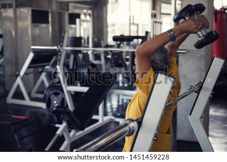 Old senior man exerise raising dumbbell by both hands for arm muscular building with fitness gym equipment background. Bodybuilding and healthy happy lifesytle for elderly.