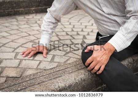 old senior man falling down, retired senior pensioner man accident; elderly old senior man injury, old senior man falls down and breaks his leg bone or knee joint; health or accident insurance concept