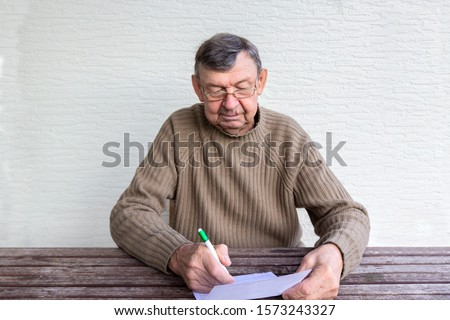 Old senior man fills in utility bills on wooden table. Planning month budget, calculating expen. Wrinkled palm of close up, copy space