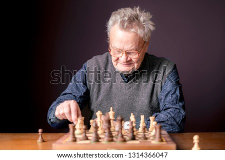 old senior man hold chess piece and think about next move