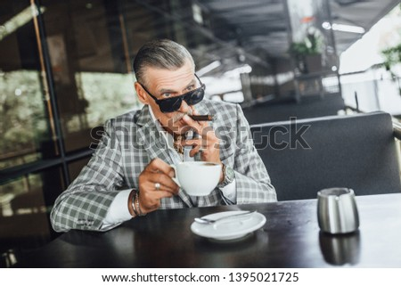 Old senior man holding a cigarette sitting on a balcony and drinking latte