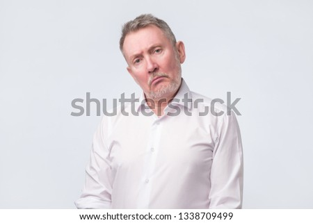 Old senior man in white shirt with serious and sad expression.