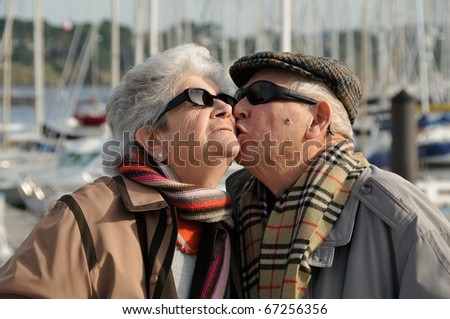 Old senior man kissing his wife at the yacht harbor.