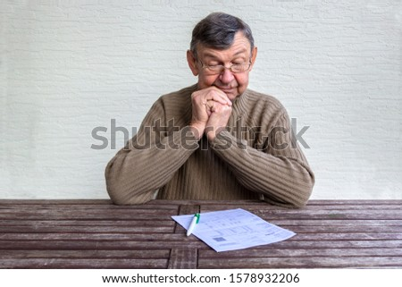 Old senior man looks with surprise on utility bills on wooden table. Planning month budget, calculating expen. Wrinkled palm of close up, copy space