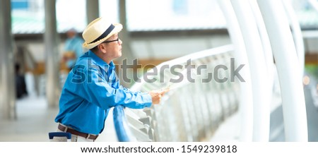 Old senior man of backpackers holding in hands travel map and walking by the city. Happy Travel and tourism concept.- panoramic web banner with copy space