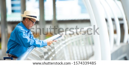 Old senior man of backpackers holding in hands travel map and walking by the city. Happy Travel and tourism concept.