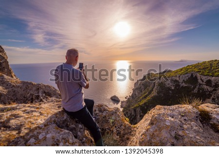 Old senior man on holidays with beautiful view on sea, taking pictures with mobile phone, enjoying retirement traveling and sightseeing