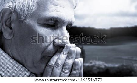 Old senior man praying