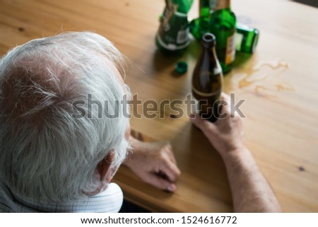 old senior man sit next to table drink alcohol bottle at home sad alone alcoholism