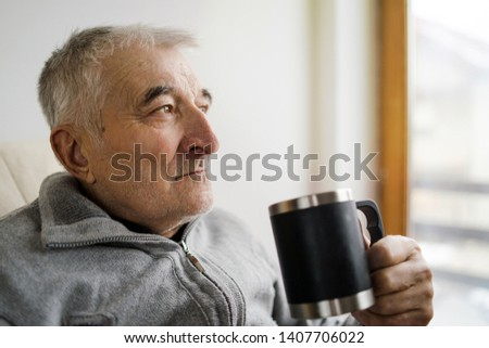 Old Senior man sitting and holding a cup of coffee tea by the window at the retirement nursing home