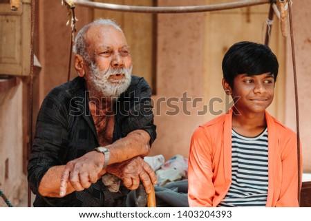 Old senior man sitting besides his grandson