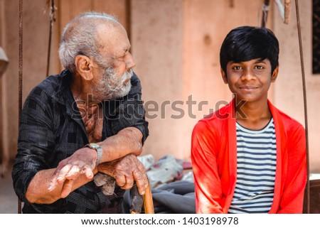 Old senior man sitting besides his grandson and talking to him