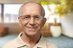 Old senior man standing on blur background