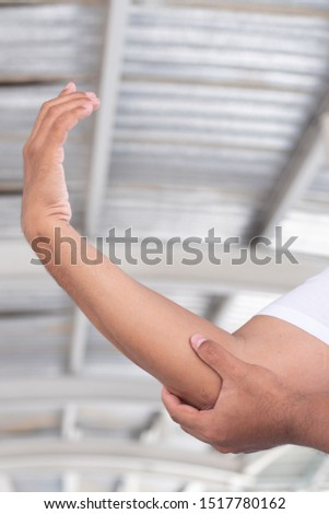old senior man suffering from elbow joint pain or injury