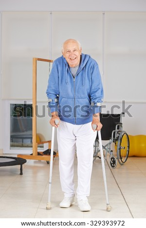 Old senior man walking with crutches in physiotherapy