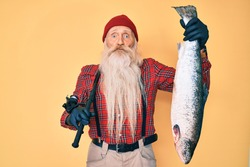 Old senior man with grey hair and long beard holding fishing rod and raw salmon puffing cheeks with funny face. mouth inflated with air, catching air.