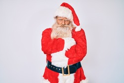 Old senior man with grey hair and long beard wearing santa claus costume with suspenders skeptic and nervous, disapproving expression on face with crossed arms. negative person.