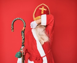 Old senior man with grey hair and long beard wearing traditional saint nicholas costume smiling cheerful playing peek a boo with hands showing face. surprised and exited