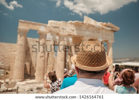 old senior man with hat 60s looking at the the Ancient Famous temple in the Acropolis area in a sunny day in the capital of Greece - Athens - travel destination concept