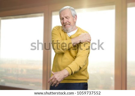 Old senior man with shoulder pain. Grandpa with shoulder inhury at home. Windows background. #1059737552