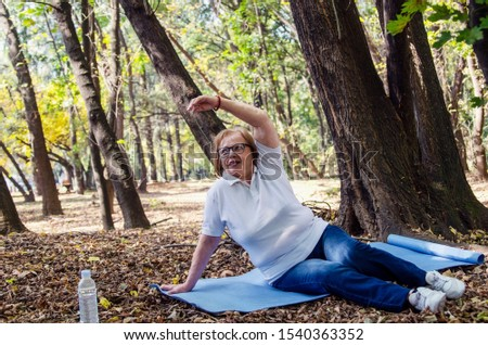 Old senior woman stretching on yoga mat outdoors in woods.Grey hair matured  female workout outdoors to lose owerweight