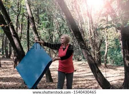 Old senior woman with yoga mat outdoors in woods going on training.Healthy lifestyle and exercise in retirement.Grey hair matured  female workout outdoors
