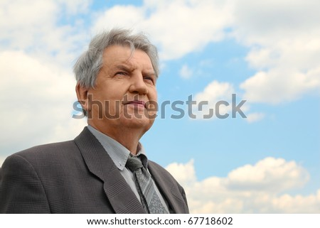 old serious senior with grey hair in suit with tie, sky with clouds