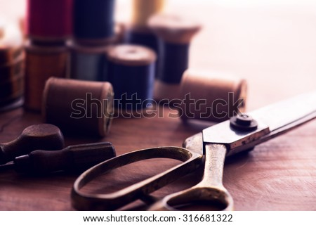 Old sew thread wooden reels or bobbins on a old grungy work table with scissors. Tailor\'s work table. textile or fine cloth making. Shallow depth of field. Intentionally shot in nostalgic muted tone.