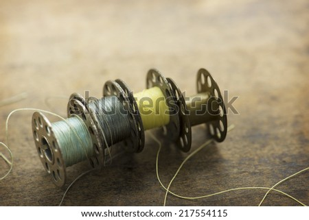 Old sewing machine bobbins with blue and yellow threads, on a old grungy work table. #217554115