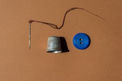 Old Sewing Needle, Thimble and Button. An Old Sewing Needle With a Red Thread, a Metal Thimble and a Blue Button Lie on a Brown Background. Vintage Items. Web Banner.