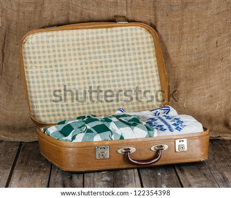Old shabby suitcase with clothes