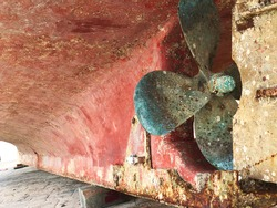 old ship not working parked on the ship yard with old brass Propeller fan blade turbine shown close up shot